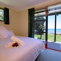 Coopers Beach Romantic Accommodation. Main bedroom in Pohutukawa Cottage